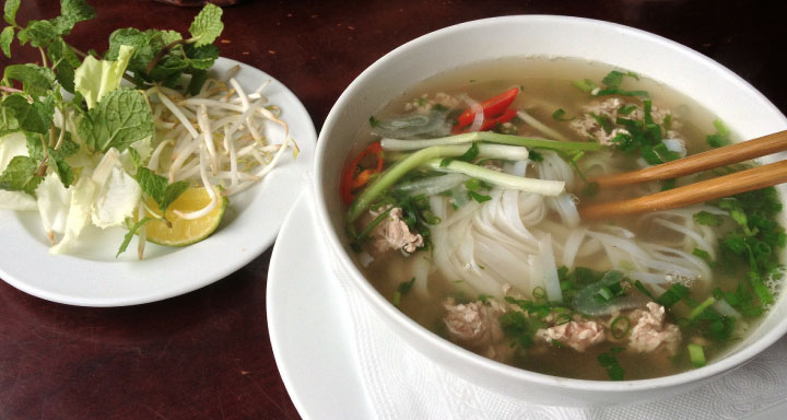 pho being served in a white bowl on a dark table