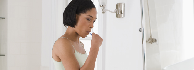 woman with short dark hair brushing her teeth in a white bathroom