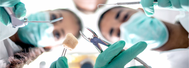 A blurry close up of a female and male dentist holding several tools for dental surgery