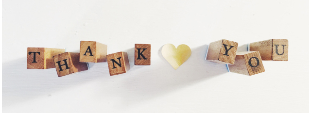 "Illustration of wooden blocks spelling out ""thank you"" with a white paper heart in between the words"