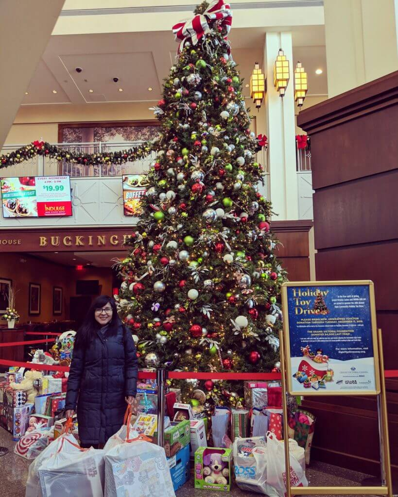 A woman with glasses standing in front of a Christmas toy drive, smiling and holding bags of toys