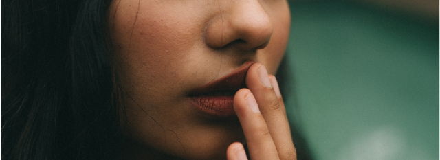 young woman touching her lip