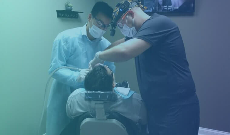 Young man sits in dentist's chair, while receiving a dental exam by a dentist and hygienist