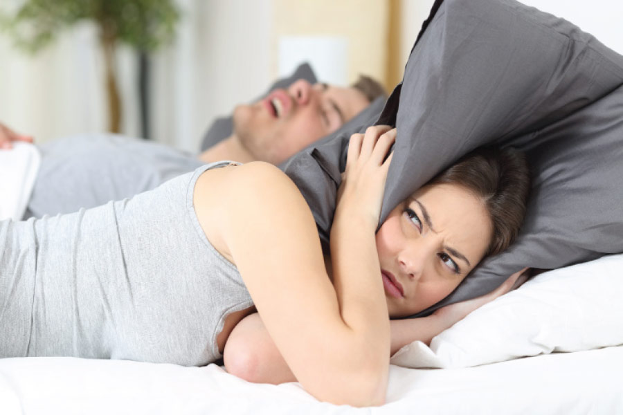 woman covers her head with a pillow to block out her partners snoring